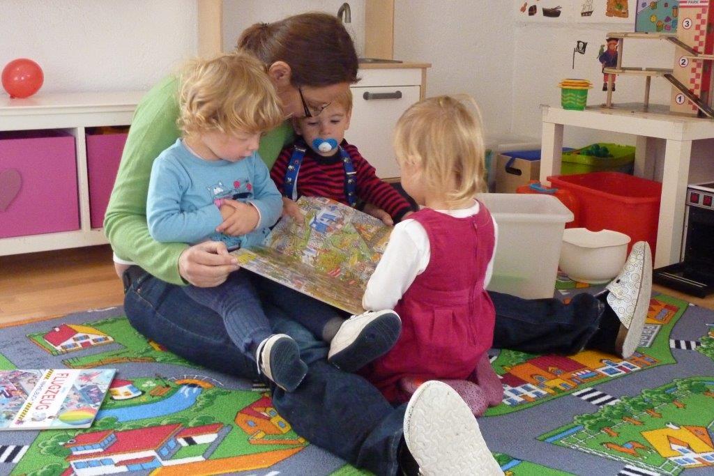 Tagesmutter mit 3 Kindern beim Lesen